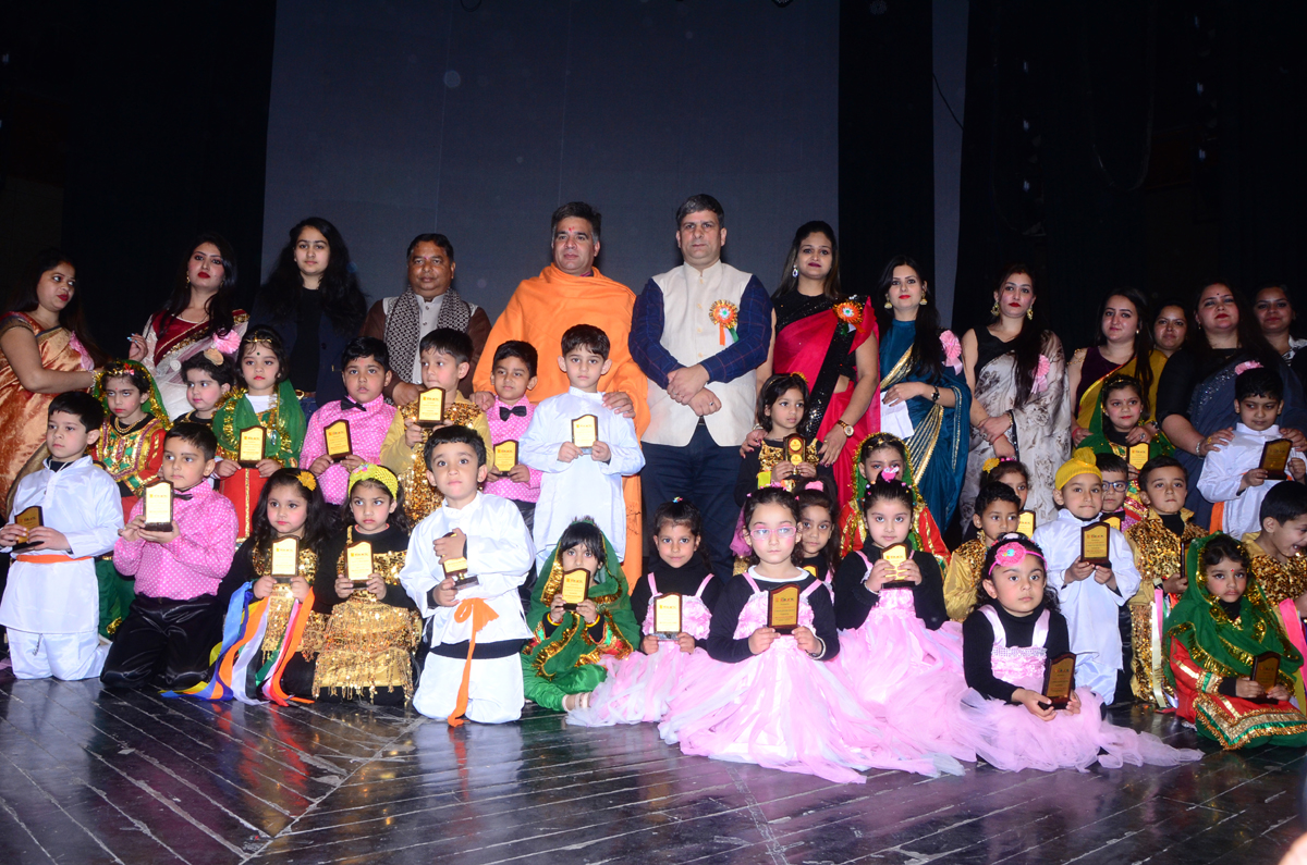 Children in colourful attires posing along with chief guest and other dignitaries during Annual day celebration at Abhinav Theatre in Jammu.