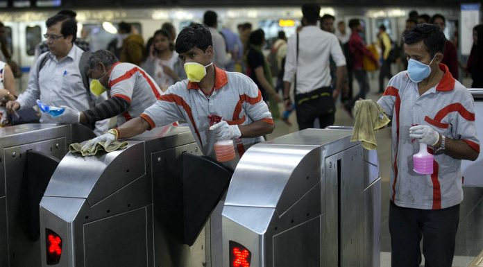 Metro station workers spray disinfectant as a precaution against Coronavirus in New Delhi on Friday.