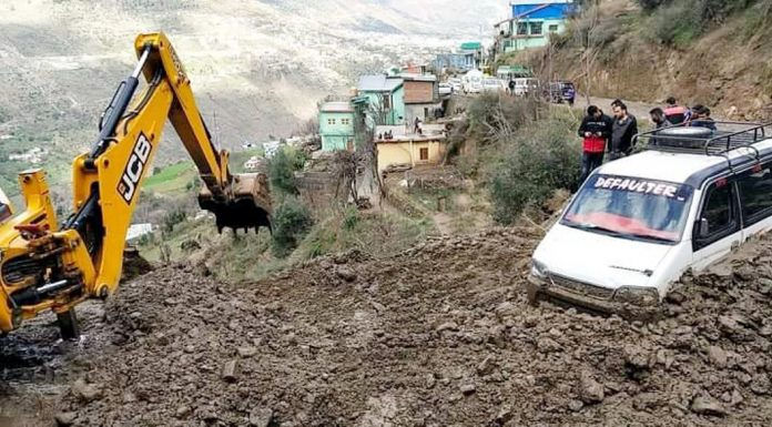 Men and machinery at work to clear debris from a blocked road in Doda on Friday.