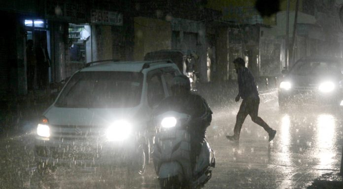 Vehicles move with headlights on in Jammu city amid heavy rains on Friday evening. -Excelsior/Rakesh