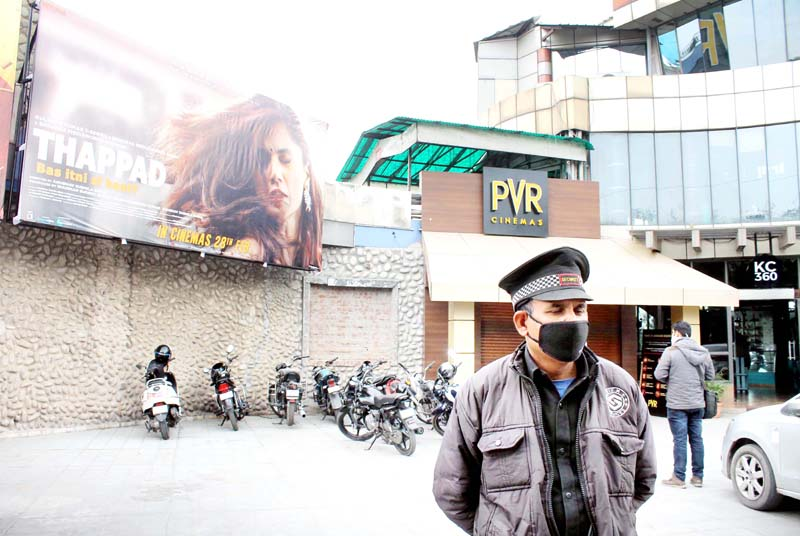 Security guard wearing mask standing outside PVR Cinema in Jammu on Wednesday. (UNI)