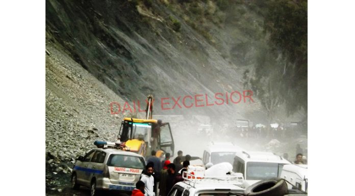Vehicles waiting for stoppage of shooting stone incidents at Cafeteria Morh on Jammu-Srinagar National Highway on Sunday. —Excelsior/Parvaiz Mir