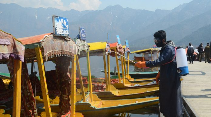 Shikaras being sanitized by SMC workers at Dal lake in Srinagar on Wednesday. —Excelsior/Shakeel