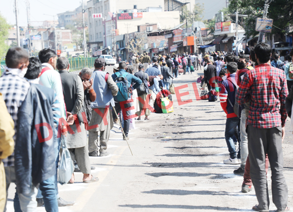 Stranded people line up for registration at Jammu Bus Stand to get transport facility for reaching at their homes. —Excelsior/Rakesh