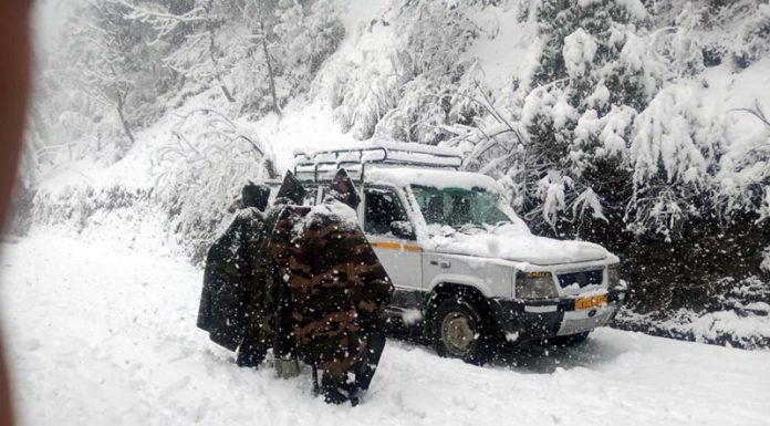 Army troops with police rescuing stranded passengers in Dera Ki Gali area of Poonch on Sunday. Another pic on page 6 (UNI)