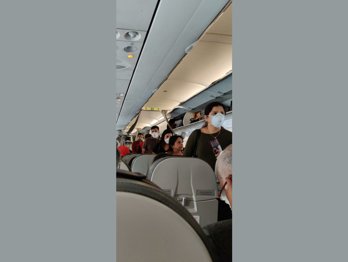 Passengers wearing masses to get ready to deplane from Vistara flight after landing at Jammu airport on Sunday afternoon.