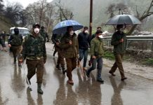 Police patrolling Srinagar roads amid rains on Tuesday. (UNI)