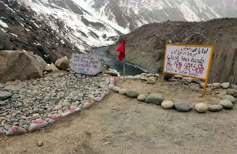Youth of village Latoo near the Line of Control in Kargil put a water tank and soap at the entery point with a slogan on a rock that no one is allowed to entry the village before he washes hands as a measure to combat Coronavirus scare.(UNI)