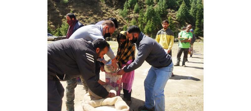 BJP workers distributing ration among needy persons in Bhadarwah. —Excelsior/Tilak Raj
