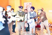 SSP Jammu Sridhar Patil distributing ration among needy people in R S Pura on Sunday.