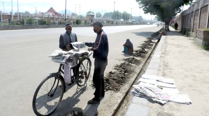 A hawker selling newspapers on Batamaloo road in Srinagar amid strict lockdown on Wednesday. (UNI)