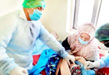 Newly born being attended upon by health staff and mother in quarantine in Kargil on Wednesday. -Excelsior/Basharat Ladakhi
