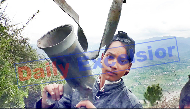 A boy shows large mortar shell fired by Pakistan army in Mankote sector of Poonch on Tuesday. -Excelsior/Rahi Kapoor
