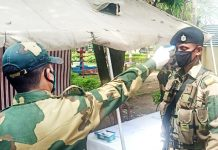 A BSF jawan checking his colleague at Panjtila check point in border area of Samba to ensure safety against Coronavirus. -Excelsior/ Gautam