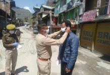 Cops give mask to a youth during lockdown in Doda town on Wednesday. — Excelsior/Rafi Choudhary