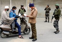 A security personnel checking the documents of a scooterist at Budshah Chowk in Srinagar amid lockdown. (UNI)