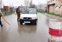 A vehicle being intercepted during lockdown in Baramulla on Tuesday. -Excelsior/ Aabid Nabi