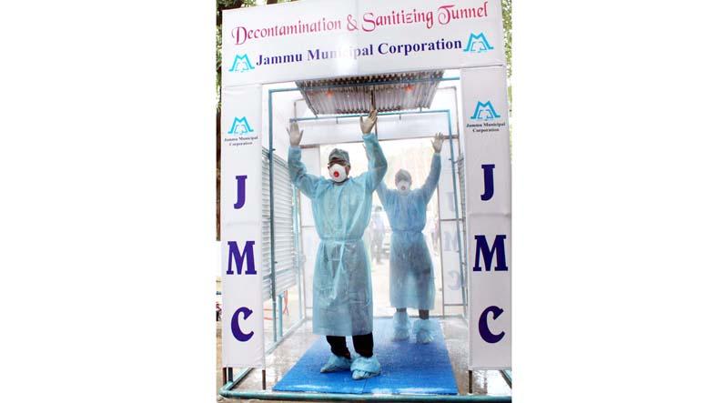 Health professionals passing through Decontamination & Sanitizing Tunnel established at GMC Jammu. -Excelsior/Rakesh