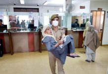 A cop takes senior citizen to the treasury for withdrawal of pension in R S Pura on Saturday.