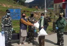 CRPF personnel distribute ration among needy people in Bhaderwah on Thursday. -Excelsior/Tilak Raj