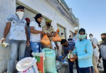 Police personnel and civilians distribute ration among needy persons in Ramgarh area of Samba district on Wednesday. — Excelsior/Abhishek Badyal