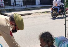 A cop provides eatables to a beggar in R S Pura on Thursday.