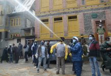 SMC workers spray disinfectant in Srinagar. — Excelsior/Shakeel