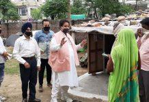 Former Minister and senior Congress leader Raman Bhalla distributing eatables among needy at Marble Market slums in Gandhi Nagar constituency.