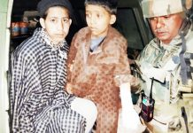 An Army soldier with 5 year old fire victim after providing her treatment at hospital.