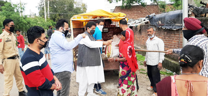 Former Minister, Raman Bhalla distributing food items among migrant labourers at Channi Himmat in Jammu.