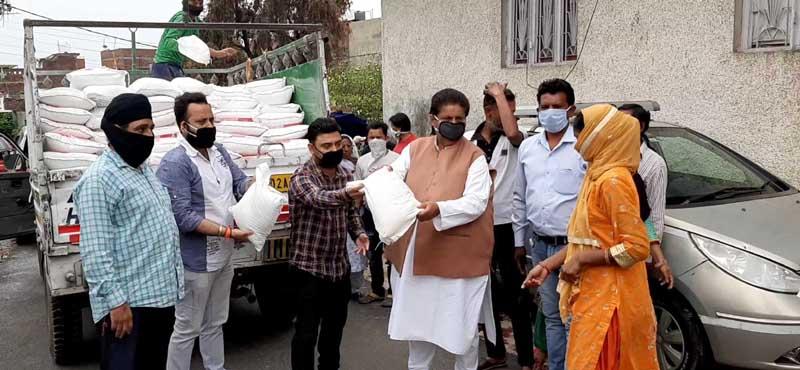 Senior Congress leader, Raman Bhalla distributing ration to poor families of Gandhi Nagar on Tuesday.