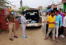 Excise Department officials distributing masks among the people.