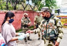 Sewa Bharti members distributing tea and biscuits among security forces personnel.