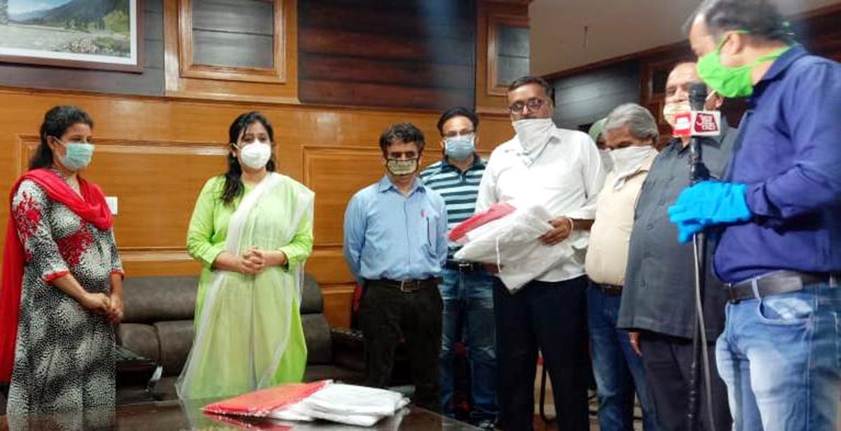 Entrepreneurs handing over PPE kits to Director I&C, Anoo Malhotra at Jammu.