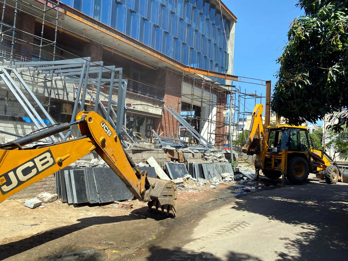 JCB machines demolishing a violative portion of the commercial building in Channi Himmat area of Jammu.