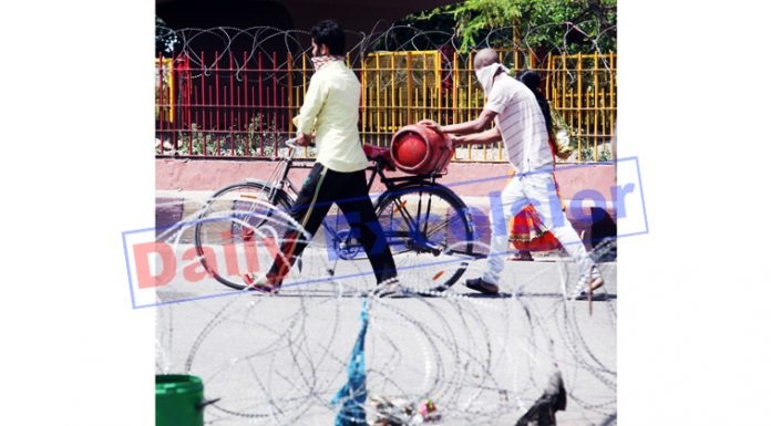 A man carries LPG cylinder on bicycle during lockdown in Jammu on Friday. -Excelsior/Rakesh