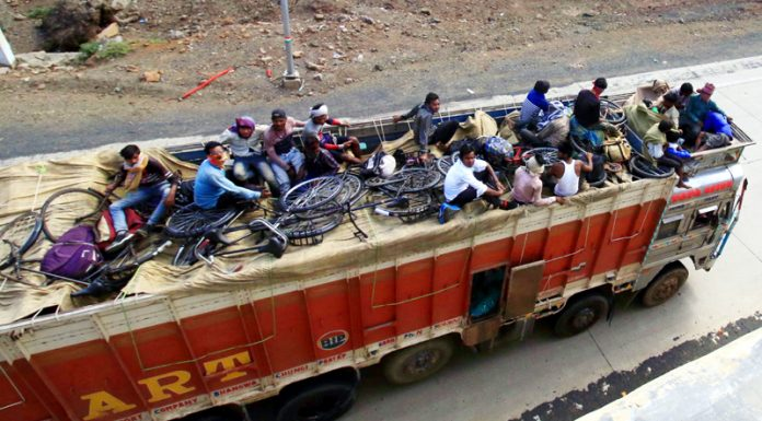 Migrant labourers travelling on a truck to reach their hometown during the nationwide lockdown in Jabalpur on Tuesday. (UNI)