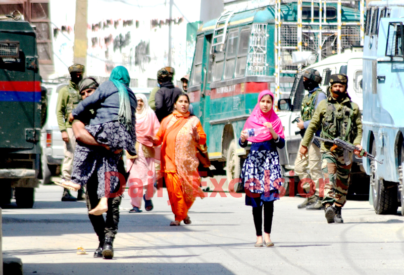 Security personnel evacuate an old woman from the encounter site at Nawakadal in Srinagar on Tuesday. -Excelsior/Shakeel