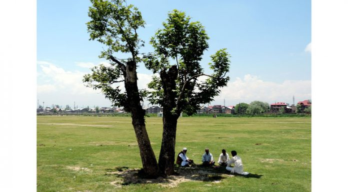 Elderly people sitting under the shade of a tree gossiping in Eidgah in downtown Srinagar where Eid Nimaz was not allowed amid lockdown on Sunday. (UNI)