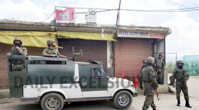Security forces stands near the site of grenade blast at Pakherpora, Budgam on Tuesday. -Excelsior/Younis Khaliq
