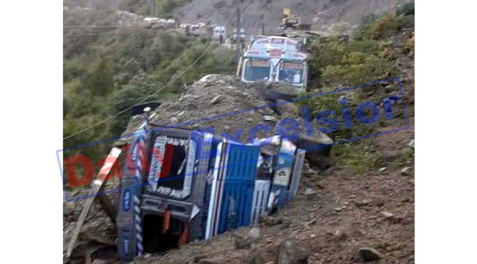 Trucks trapped in landslides at Seri on Jammu-Srinagar NH in Ramban sector on Saturday. -Excelsior/Parvez Mir