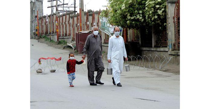 People carrying milk pots walking at Khan-e-Kah-Molla road in downtown Srinagar on Saturday. (UNI)