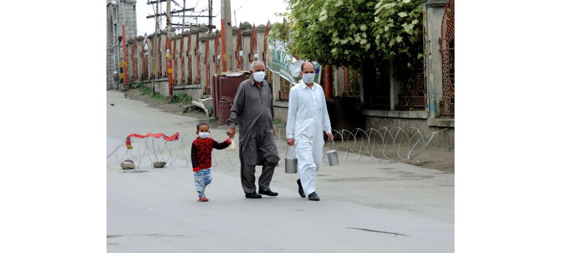 People carrying milk pots walking at Khan-e-Kah-Molla road in downtown Srinagar on Saturday. (UNI)