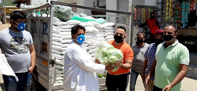 Former Minister Raman Bhalla distributing essential items among needy in Gandhi Nagar constituency on Monday.