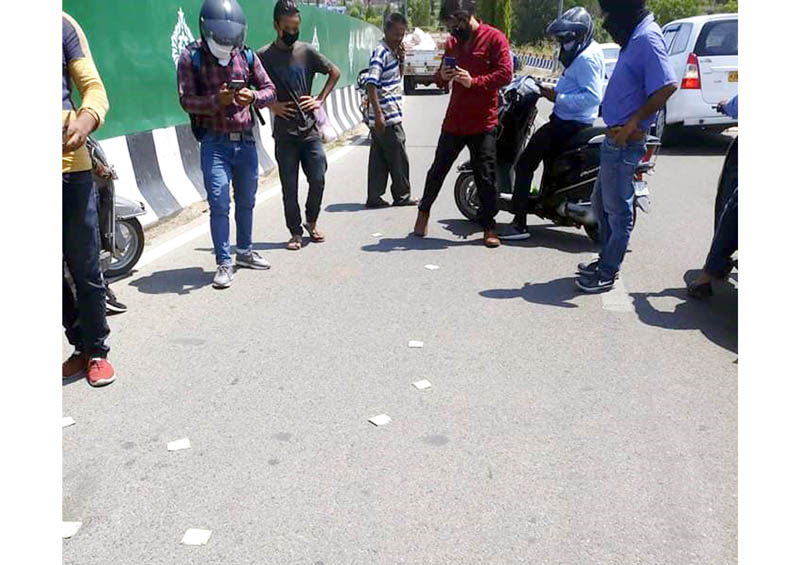 People watching Rs.500 currency notes scattered on road in Jammu on Tuesday.