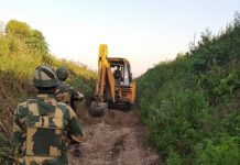 BSF personnel guarding a JCB engaged in desilting work of Ranbir Canal.