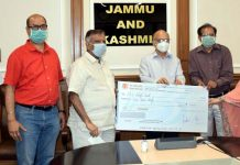 Director Industries, Anu Malhotra and others presenting a cheque to Advisor K K Sharma at Jammu on Wednesday.