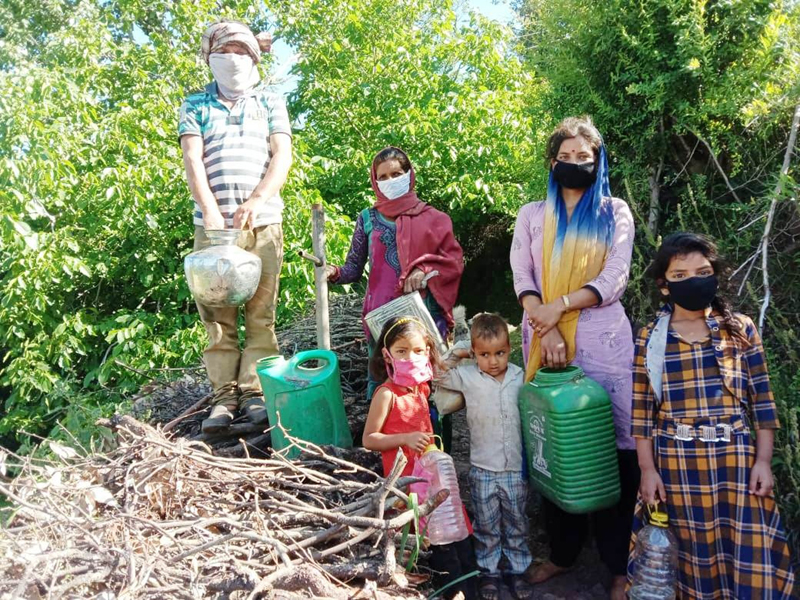 Women alongwith kids on way to fetch water from natural sources in Panchari tehsil of Udhampur.