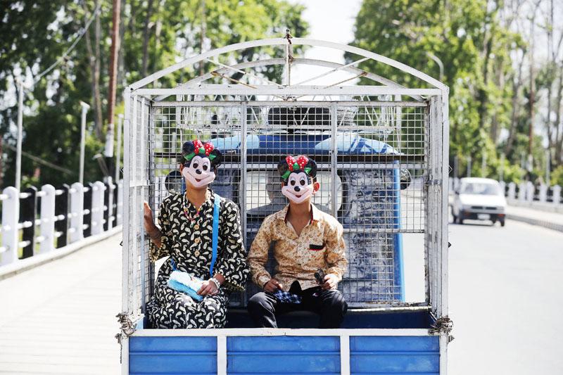Kids wearing joker masks enjoying an unusual ride in Srinagar. -Excelsior/ Shakeel