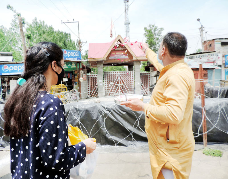 Kashmiri Pandit pilgrims performing puja outside the main gate of Mata Kheer Bhawani Temple at Tulamulla in Central Kashmir on Saturday. -Excelsior/ Shakeel